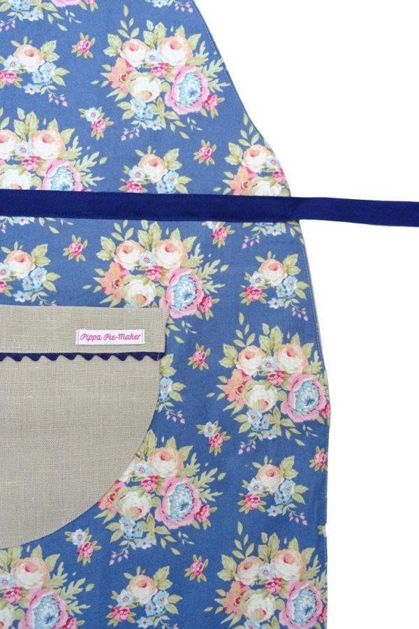 Florentina ist eine Wendeschürze. Innen ganz klassisch aus Leinen, außen mit blauem Blumenmuster und Tasche.